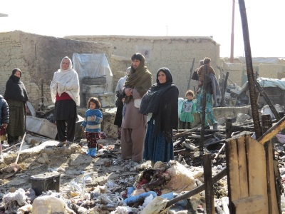 Refugees in the Chaman e Babrak camp stand amid the rubble