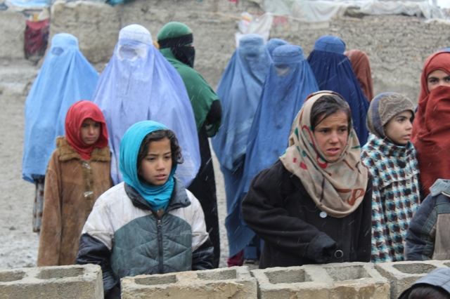 Girls and mothers, waiting for their duvets, in Kabul