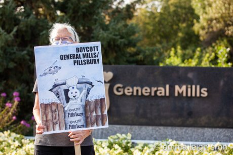 A protest sign at General Mills headquarters, Minneapolis, shows a Pillsbury Doughboy waving from an Israeli military watchtower. Photo: Emma Sron. More photos at emmasron.com
